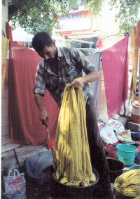 Man in market dying fabric